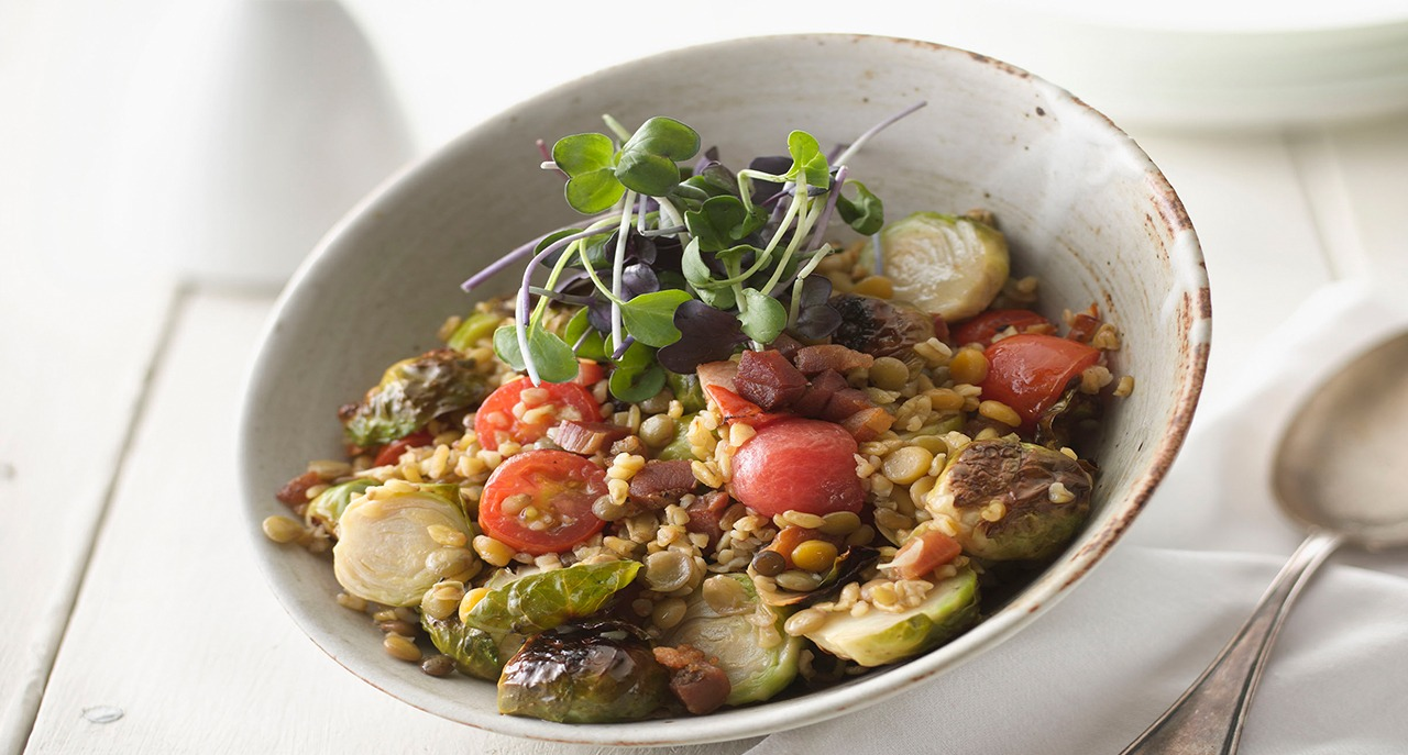 Blistered brussel sprouts freekah and lentil salad in bowl
